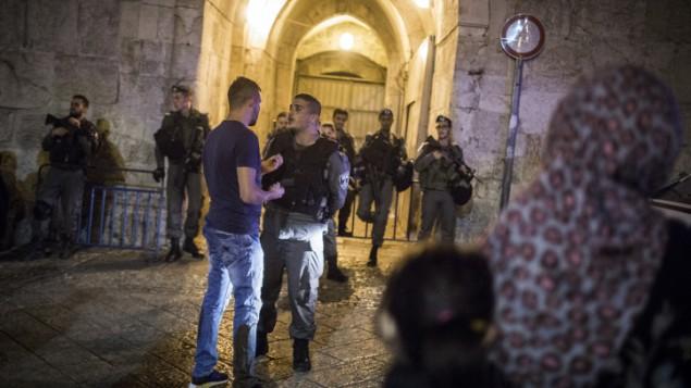 فلسطينيون ينتظرون امام باب الزاهرة بينما تغلق عناصر الامن البلدة القديمة في القدس اثناء البحث عن مشتبه بعد هجوم طعن، 2 مايو 2016 (Hadas Parush/Flash90)