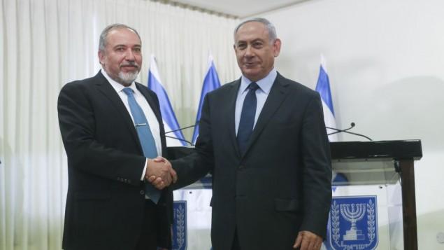 رئيس الوزراء بنيامين نتنياهو يصافح رئيس حزب يسرائيل بيتينو بعد التوقيع على اتفاق ائتلافي في الكنيست، 25 مايو 2016 (Yonatan Sindel/FLASH90)