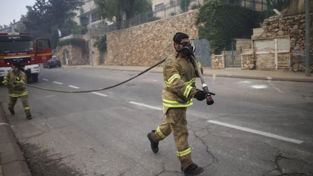 رجال الاطفاء يعملون على اخماد حريق بالقرب من حي راموت في القدس، 26 مايو 2016 (Yonatan Sindel/Flash90)