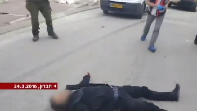 منفذ الهجوم ملقى على الأرض على مسافة بعيدة من السكين في الخليل في 24 مارس، 2016. (لقطة شاشة من القناة 2)