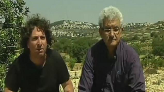 المستوطن اليهودي إباز كوهين، من اليسار، والعضو في منظمة التحرير الفلسطينية محمد البيروتي يجلسان معا بالقرب من إفرات، في الضفة الغربية. الرجلان ناشطان في الحركة الجديدة 'دولتان ووطن واحد' يسيران باتجاه الجدار الفاصل الذي يفصل الضفة الغربية عن إسرائيل. (لقطة شاشة من القناة 2)