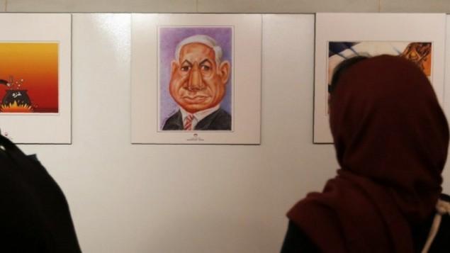 إمرأة إيرانية تقف أمام صورة كاريكاتورية لرئيس الوزراء بينيامين نتنياهو في المعرض الدولي الثاني للرسوم الكاريكاتورية عن المحرقة في طهران، 14 مايو، 2016. (AFP PHOTO / ATTA KENARE)