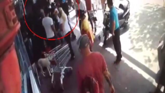 صورة لرجال شرطة مزعومين يقومون بالإعتداء بالضرب على شاب عربي في تل أبيب، 22 مايو، 2016. (لقطة شاشة: القناة 2)