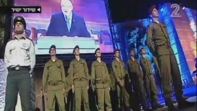 جنود إسرائيليون يقفون خلال إلقاء رئيس الدولة رؤوفين ريفلين كلمته مع إنطلاق فعاليات إحياء ذكرى المحرقة في متحف ياد فاشيم في القدس، 4 مايو، 2016. (لقطة شاشة: القناة 2)