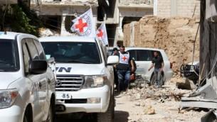 مركبات تابعة لمنظمة الصليب الأحمر الدولية والأمم المتحدة تنتظر في أحد الشوارع بعد دخول قافلة مساعدات إلى بلدة داريا، جنوب غرب العاصمة السورية دمشق، 1 يونيو، 2016. (AFP PHOTO / Fadi Dirani)