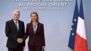وزيرة خارجية الإتحاد الأوروبي فيديريكا موغيريني، من اليمين، تلقى ترحيبا من وزير الخارجية الفرنسي جان مارك آيرولت قبيل  المؤتمر الدولي الذي يهدف إلى إحياء مفاوضات السلام بين الإسرائيليين والفلسطينيين في باريس، 3 يونيو، 2016. (AFP/Pool/Stephane de Sakutin)