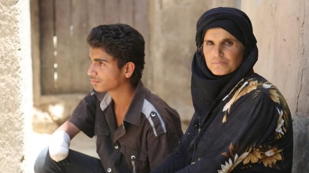 الشاب بشار قاسم، الذي قام تنظيم الدولة الإسلامية بقطع يده، مع والدته، في بلدة الهول في محافظة الحسكة في سوريا، 31 مايو 2016 (DELIL SOULEIMAN / AFP)