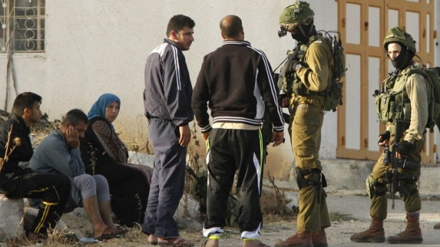 جنود إسرائيليون يتحدثون مع فلسطينيين بعد دخول الجيش الإسرائيلي قرية يطا في الضفة الغربية، 6 يونيو، 2016. (AFP PHOTO / HAZEM BADER)