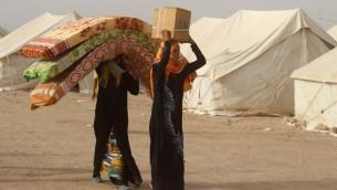 نازحون عراقيون فروا من مدينة الفلوجة، معقل تنظيم الدولة الإسلامية، يحملون الفرشات ورزم مساعدات في مخيم يقع حوالي 30 كلم جنوب المدينة، 9 يونيو 2016 (MOADH AL-DULAIMI / AFP)