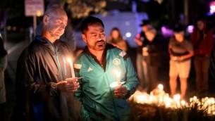 اشخاص يضيؤون الشموع تضامنا مع ضحايا هجوم إطلاق النار في أورلاندو خلال وقفة تضامنية في سان دييغو، كاليفورنيا، 12 يونيو، 2016. (AFP PHOTO / Sandy Huffaker)
