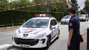 سيارة شرطة تغادر شارع مغلق بعد هجوم في مانيانفيل، بالقرب من باريس، 14 يونيو 2016 (AFP PHOTO / MATTHIEU ALEXANDRE)