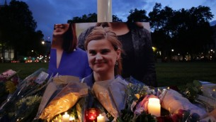 أزهار وشموع تم وضعها إلى جانب صورة لنائبة البرلمان العمالية القتيلة جو كوكس خلال وقفة تضامنية في ساحة البرلمان في لندن، 16 يونيو، 2016. (AFP PHOTO / DANIEL LEAL-OLIVAS)