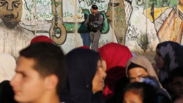 شرطي حدود اسرائيلي يراقب بينما يمر فلسطينيين عبر حاجز قلنديا في الضفة الغربية بطريقهم الى ثاني صلاة جمعة خلال شهر رمضان، 17 يونيو 2016 (AFP /ABBAS MOMANI)