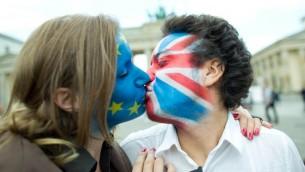 زوج رسما اعلام بريطانيا والاتحاد الاوروبي على وجهيهما يتبادلان القبل في برلين، 19 يونيو 2016 (JÖRG CARSTENSEN / DPA / AFP)