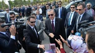 الرئيس التركي رجب طيب أردوغان، في الوسط، يحيي مؤيديه عند وصوله إلى حفل افتتاح مسجد بايزيد (يلدريم بايزيد) في مطار إيسينبوغا الدولي في أنقرة، 23 يونيو، 2016. (Adem Altan/AFP)