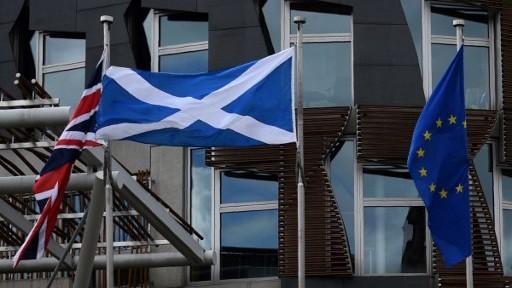 العلام الاسكتلندي بين علمي الاتحاد الاوروبي وعلم بريطانيا امام البرلمان الاسكتلندي، 25 يونيو 2016 (OLI SCARFF / AFP)