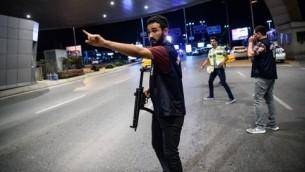 شرطي تركي امام مدخل مطار اتاتورك الرئيسي في اسطنبول بعد تفجير انتحاري ادى الى مقتل 36 شخصا على الاقل، 28 يونيو 2016 (AFP/ OZAN KOSE)