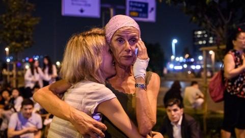 مسافرون يتعانقون امام مدخل مطار اتاتورك الرئيسي في اسطنبول بعد تفجير انتحاري ادى الى مقتل 36 شخصا على الاقل، 28 يونيو 2016 (AFP/ OZAN KOSE)