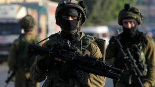 من الأرشيف: جنود إسرائيليون يقومون بدورية في شارع، شرقي غرب مدينة نابلس في الضفة الغربية، 3 أكتوبر، 2015، خلال عمليات بحث عن فلطسيني مشتبه به بقتل الزوجين الإسرائيليين إيتام ونعمة هينكين. (AFP PHOTO/JAAFAR ASHTIYEH)