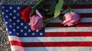 الأزهار والعلم الأمريكي بالقرب من نادي Pulse الليلي حيث قام عمر متين بقتل 49 شخصا في 13 يونيو، 2016 في مدينة أورلاندو بدولاية فلوريدا. ( Joe Raedle/Getty Images/AFP)