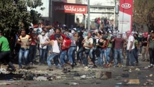 متظاهرون فلسطينيون يرشقون القوات الإسرائيلية بالحجارة عند حاجز حوارة، جنوبي مدينة نابلس في الضفة الغربية، 11 أكتوبر، 2015. (Flash90)