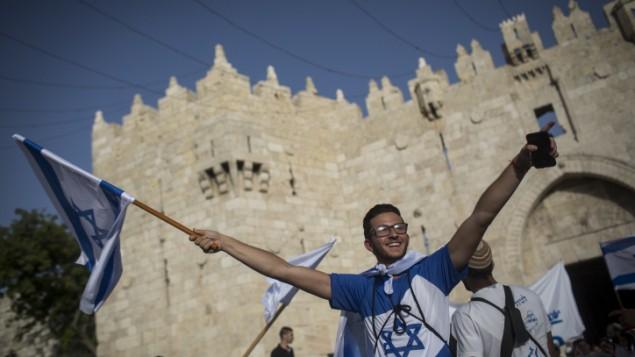 """آلاف الإسرائيليين، معظمهم شبان وفتيان يهود، يلوحون بالأعلام الإسرائيلية خلال مرورهم عبر باب العامود دخولا إلى الحي الإسلامي في طريقهم إلى الحائط الغربي للإحتفال ب""""يوم القدس""""، 5 يونيو، 2016.  (Hadas Parush/Flash90)"""