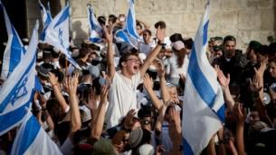 """الآلاف من الفتيان اليهود يلوحون بالأعلام الإسرائيلية خلال الإحتفالات ب""""يوم القدس"""" ويرقصون ويسيرون من خلال باب العامود وصولا إلى الحائط الغربي، 5 يونيو، 2016. (Nati Shohat/Flash90)"""