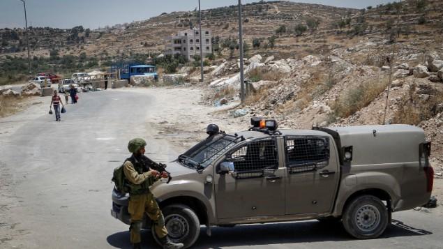 الجنود الإسرائيليون يقفون عند حاجز في مدخل بلدة يطا الفلسطينية في الضفة الغربية، 9 يونيو، 2016. (Wisam Hashlamoun/Flash90)