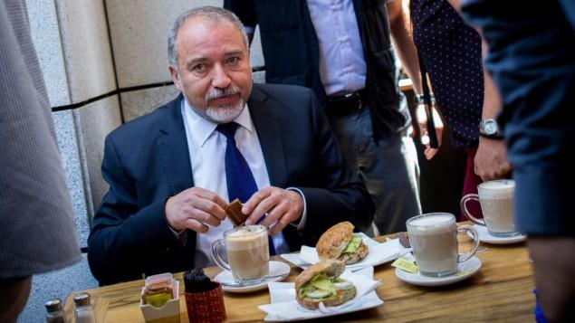 لإظهار الدعم بعد يوم من وقوع هجوم إطلاق دام في المكان، وزير الدفاع أفيغدور ليبرمان يتناول القهورة في مجمع سارونا في تل أبيب، يوم الخميس، 9 يونيو، 2016. (Miriam Alster/Flash90)