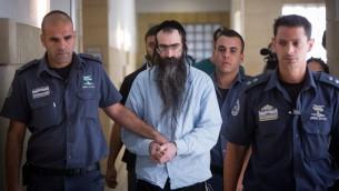 يشاي شليسل، في الوسط، خلال اقتياده إلى قاعة المحكمة المركزية في القدس، 26 يونيو، 2016. (Yonatan Sindel/Flash90)