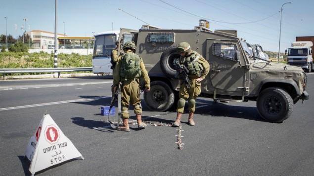 جنود إسرائيليون يضعون حاجزا عند مدخل مستوطنة كريات أربع في الضفة الغربية في 30 يونيو، 2016، بعد أن قام فتى فلسطيني بطعن وقتل فتاة إسرائيلية تبلغ من العمر 13 عاما هناك. (Wisam Hashlamoun/Flash90)