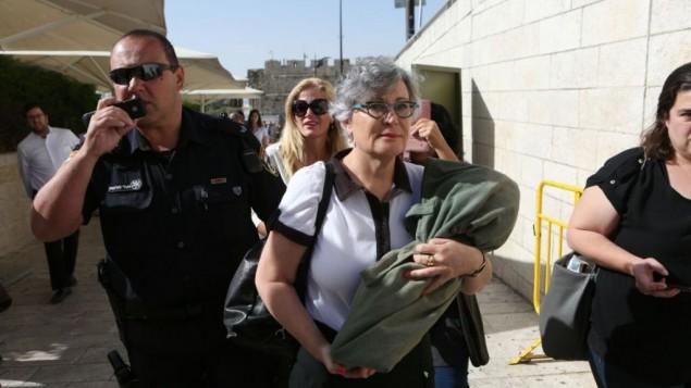 المديرة التنفيذية لمنظمة 'نساء الحائط' ليزلي ساكس تحمل لفافة توراة بينما يرافقها شرطي إلى خارج باحة الحائط الغربي، 7 يونيو، 2016. (Michal Fattal)