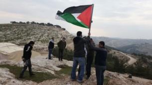 نشطاء فلسطينيون يضعون علما في E1 شرقي القدس، التي تقع في المنطقة (C) بالضفة الغربية. (photo credit: Issam Rimawi/Flash90)