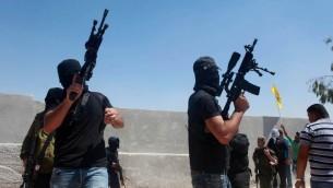 مسلحون فلسطينيون يطلقون الرصاص في الهواء خلال تشييع جثمان ثلاثة رجال قتلوا برصاص جنود اسرائيليين في مخيم قلنديا، بالقرب من رام الله، 26 اغسطس 2013 (Issam Rimawi/Flash90)