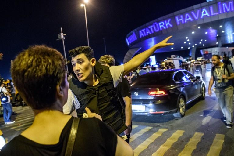 """شرطي تركي يوجه أحد المسافرين في مطار """"أتاتورك"""" في إسطنبول، 28 يونيو، 2016، بعد إعتداء وقع في أكبر مطار في تركيا. (AFP PHOTO / OZAN KOSE)"""