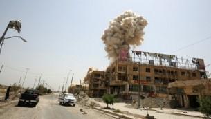 الدخان يتصاعد من مدينة الفلوجة بعد قصف القوات العراقية مبنى مفخخ بعد استيلائها على المدينة من التنظيم الجهادي، 30 يونيو 2016 (AHMAD AL-RUBAYE / AFP)