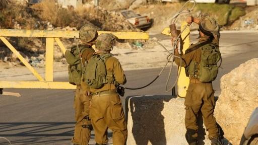 جنود اسرائيليون يقيمون حاجزا امنيا عند المدخل الجنوبي لمدينة الخليل في الضفة الغربية، 2 يوليو 2016 (HAZEM BADER / AFP)