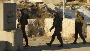 صورة توضيحية: جنود اسرائيليون يقيمون حاجزا امنيا عند المدخل الجنوبي لمدينة الخليل في الضفة الغربية، 2 يوليو 2016 (HAZEM BADER / AFP)