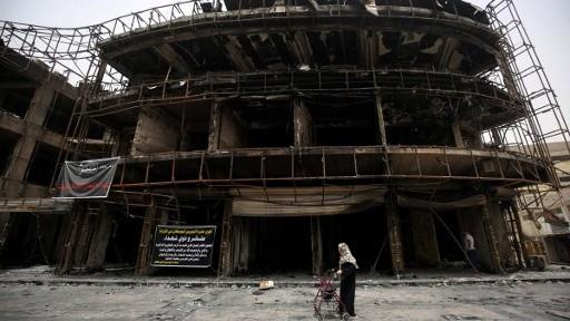 امرأة عراقية تمشي امام مبنى تضرر في التفجير الانتحاري الذي وقع في اليوم السابق في حي الكرادة في بغداد، 4 يوليو 2017 (AHMAD AL-RUBAYE / AFP)