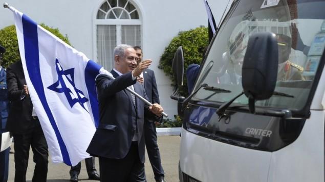بنيامين نتنياهو يحمل علم اسرائيل بعد مؤتمر صحفي مشترك مع رئيس كينيا، 5 يوليو 2016 (AFP/SIMON MAINA)