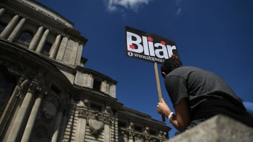 """متظاهر يحمل لافتة تم تحويل اسم توني بلير عليها الى """"بلاير""""، من خلال اللعب على كلمة """"لاير"""" أي الكاذب، بالقرب من مكان نشر تقرير التحقيق في العراق، لندن، 6 يوليو 2016 (BEN STANSALL / AFP)"""