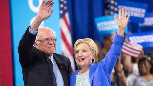 المرشحة الديمقراطية للرئاسة الديمقراطية هيلاري كلينتون وبيرني ساندرز يحيان الجماهير بعد خطاب في نيوهامبشير، 12 يوليو 2016 (JUSTIN SAGLIO / AFP)