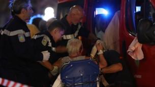 طواقم انقاذ يساعدون امرأة مصابة على الدخول الى سيارة اسعاف بعد هجوم دهس في بلدة نيس الفرنسية، 15 يوليو 2016 (AFP PHOTO / Valery HACHE)