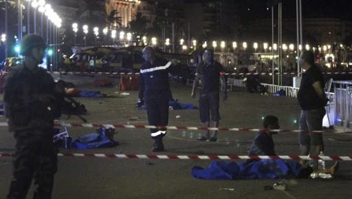 جنود وعناصر شرطة ورجال إطفال يسرون بالقرب من جثث مغطاة بأغطية زرقاء في 'متنزه الإنجليز' في مدينة نيس التي تقع في الريفييرا الفرنسية في 15 يوليو، 2016 بعد أن قامت شاحنة بدهس جمع من الأشخاص احتشدوا لمشاهدة عرض ألعب نارية. (AFP PHOTO / VALERY HACHE)