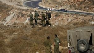 جنود اسرائيليون يقومون باخلاء جندي مصاب بعد انفجار قنبلة يدوية بالقرب من بلدة مجدل شمس في مرتفعات الجولان، 17 يوليو 2016 (AFP / JALAA MAREY)