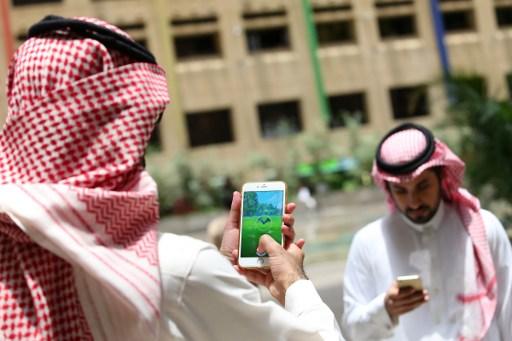 شابان سعوديان يلعبان تطبيق 'بوكيمون غو' على هاتفهما المحمولين في العاصمة الرياض، 17 يوليو، 2016. (AFP PHOTO / STRINGER)