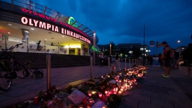 الشموع والزهور التي وُضعت أمام مركز 'أولمبيا' التجاري في 23 يوليو، 2016 في ميونج، جنوبي ألمانيا، بعد يوم واحد من قيام مسلح يحمل الجنسيتين الألماني والإيرانية بقتل 9 أشخاص وإصابة 16 آخرين. ( AFP PHOTO / dpa / Sven Hoppe)
