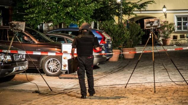 شرطي يرتدي زي واقي بالقرب من شاحة تفجير انتحاري في مبدينة انسباخ في جنوب المانيا، 25 يوليو 2016 (FRIEBE / DPA / AFP)