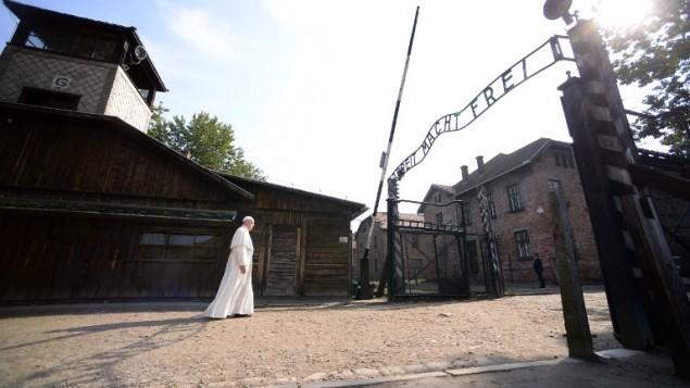 البابا فرنسيس يسير باتجاه المدخل الرئيسي المزين بكلمات 'العمل يحرر' في معسكر الموت 'اوشفيتز-بيركيناو' النازي الألمانيالقريب من كراكوفا في بولندا، 29 يوليو، 2016. (AFP PHOTO/FILIPPO MONTEFORTE)