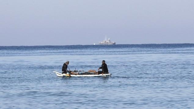 صيادان فلسطينيا يجلسان في قاربهما قبالة سواحل مدينة رفح جنوب قطاع غزة، وسفينة عسكرية إسرائيلية تظهر في الأفق، 26 مايو، 2014. (AFP/Said Khatib)